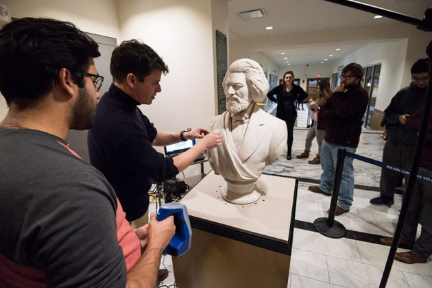 students and professor holding up a scanner next to the marble bust of Frederick Douglass