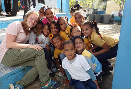 student poses with large group of children