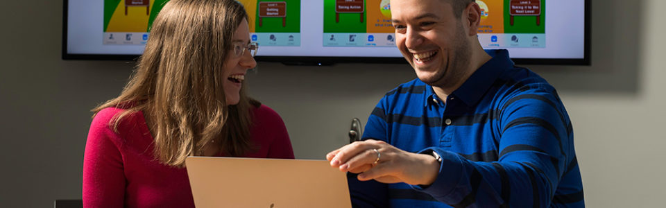 two researchers looking at a laptop and smiling