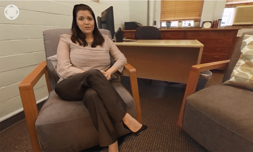 still from a video shows a doctor sitting in an office setting