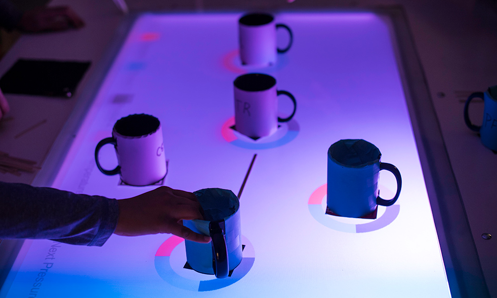 lighted glass table covered in coffee mugs