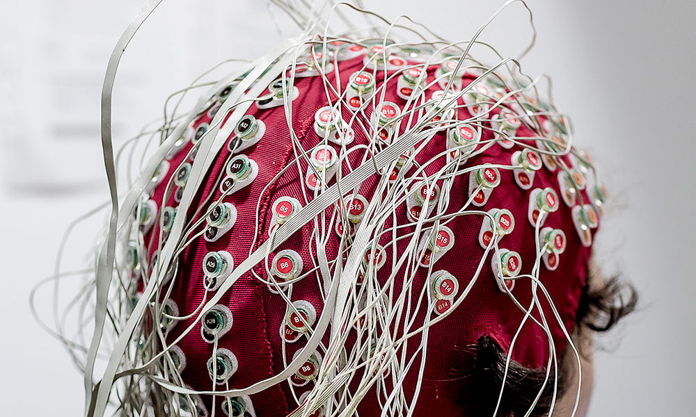 person sits with scalp cap and many wires capturing brain signals