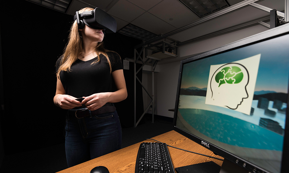 woman wearing virtual reality goggles in front of a computer screen showing an image of a brain