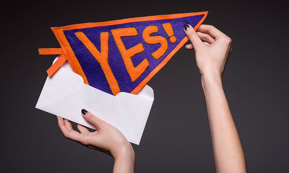 get into your dream college two hands pulling pennant out of an envelope. The pennant reads YES!