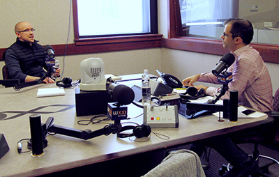 two people in a radio studio, speaking into microphones