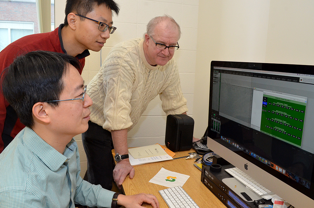 three researchers looking at a computer screen that shows sound levels