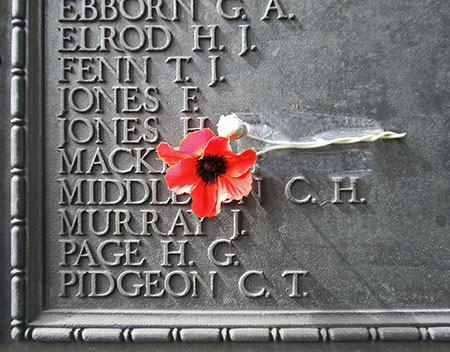 closeup of names on World War I memorial with a red poppy flower taped to the monument
