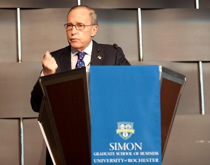 Larry Kudlow speaking at a Simon Business School podium