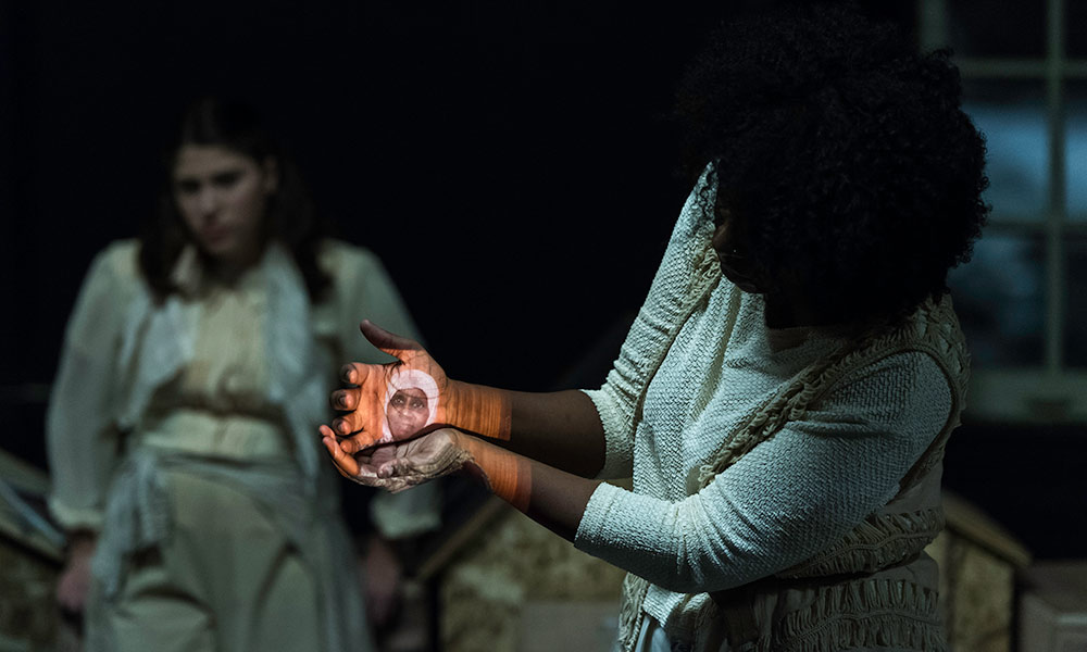 student on stage with a picture of a woman projected onto her hands