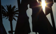 Oscars status against Hollywood skyline with sunshine and palm trees