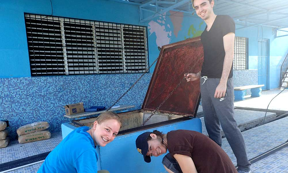 three students pose near a water filtration tank