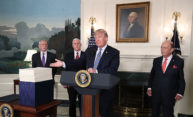 President Trump points to a large stack of papers, standing behond a podium with three other governement officials