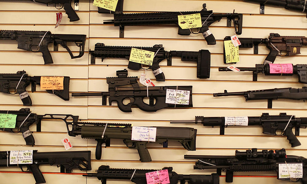 wall display in a gun store shows lots of guns