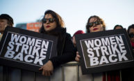two women at a rally, each holding a sign that reads WOMEN STRIKE BACK
