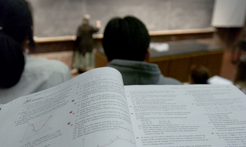 math text book in front of a student sitting in a large lecture hall