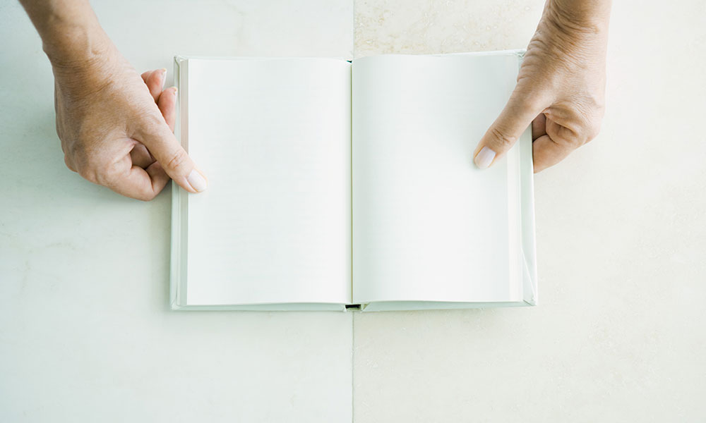 woman holding a blank book.
