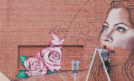 artist on a ladder, painting a mural of a woman with floweres on the side of a building