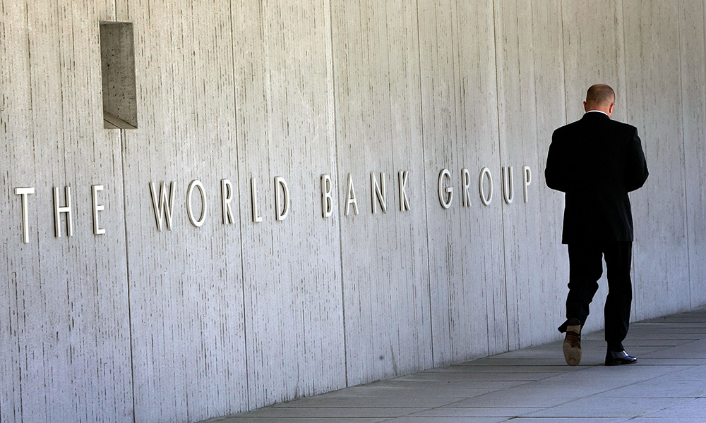 man walking in fron to building with the sign WORLD BANK