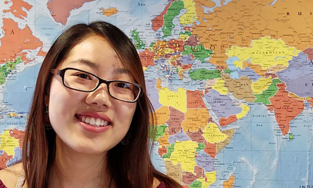still from a video featuring a young woman smiling in front of a map