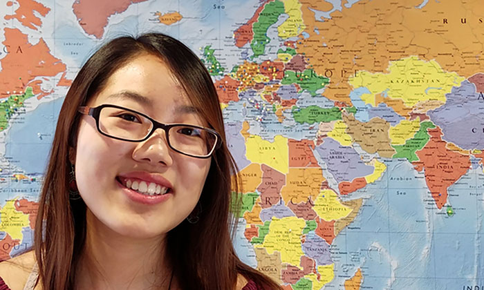 student speaking, standing in front of a world map