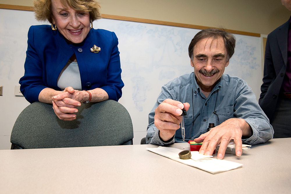 Louise Slaughter laughs and looks on as scientist drops water onto a new material