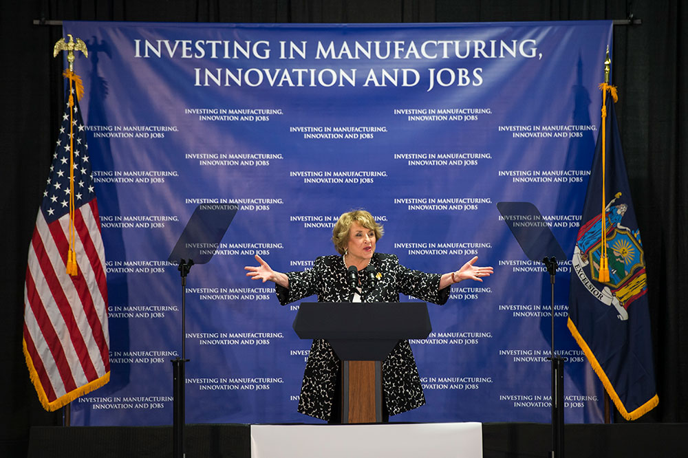 Louise Slaughter standing in front a large sign that reads INVESTING IN MANUFACTURING, INNOVATION AND JOBS