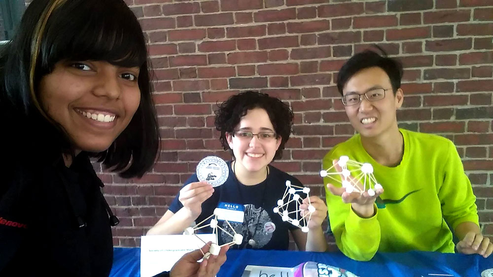 three students smiling and holding up models made with marshmallows and toothpicks