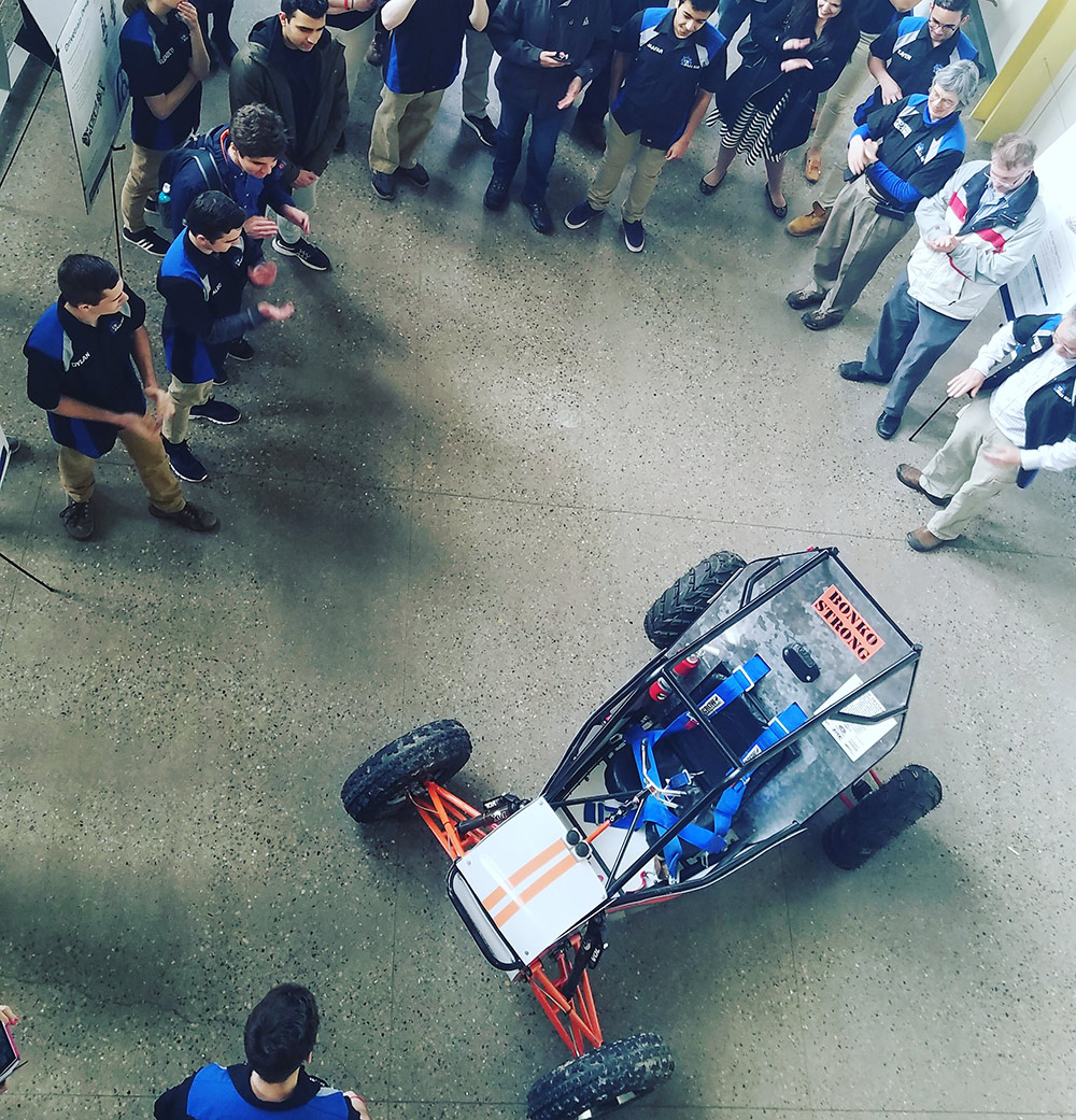 crowd of people gathered around a racing car