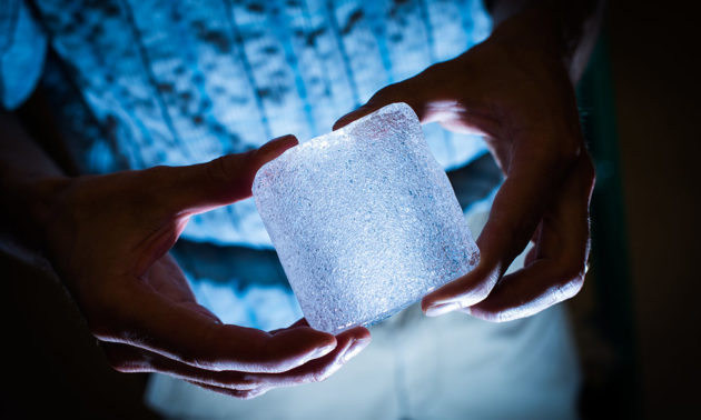 researcher holding a large cube of ice with bubble trapped in it