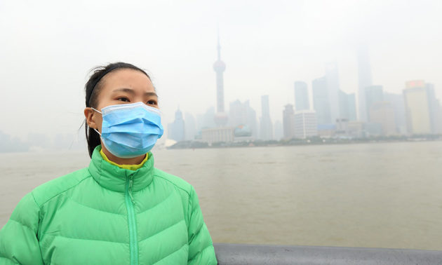 woman in a mask with polluted skyline of Beijing in the background