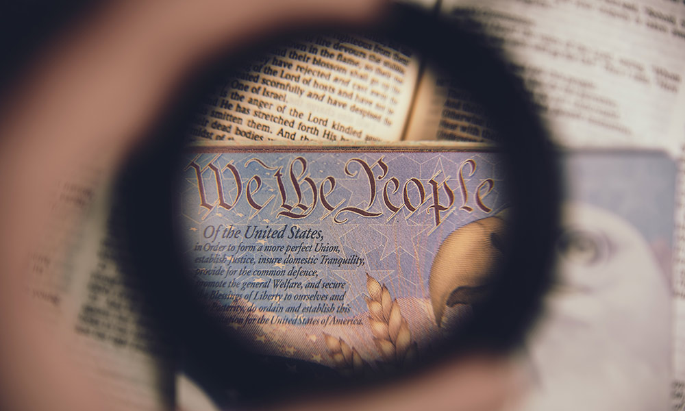 looking at the Constitution with the words WE THE PEOPLE through a magnifying glass