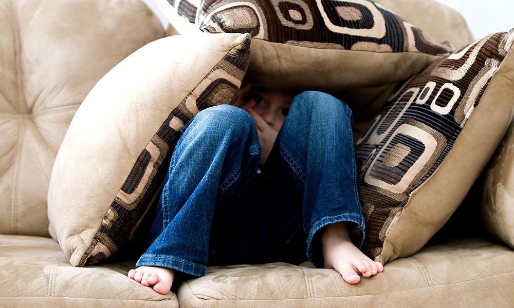 child hiding under sofa cusions