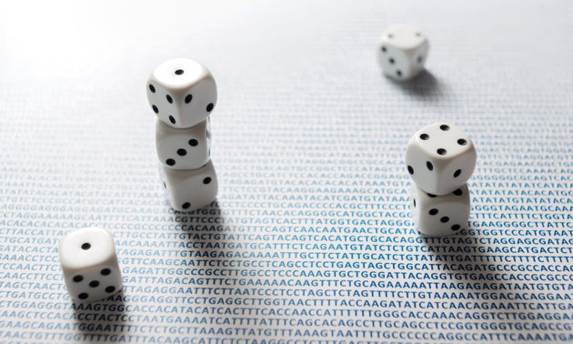 a pile of dice sitting a table covered in the A T C G letters of DNA
