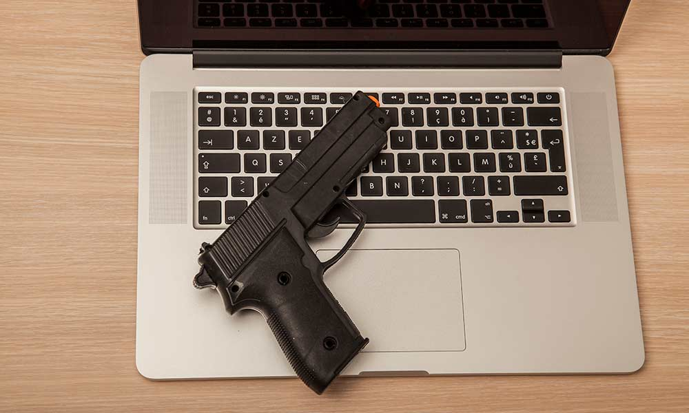 gun places on the keyboard of a laptop