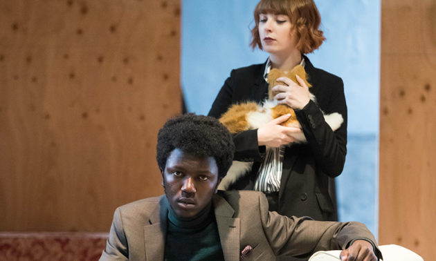 two actors on stage, one sitting on a couch, the other holding a cat