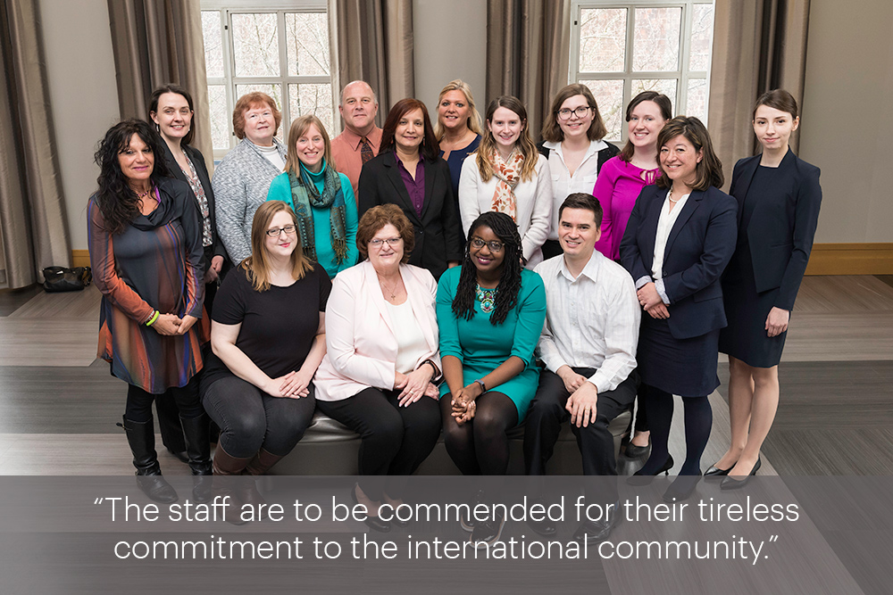 "Group portrait with the quote, ""The staff are to be commended for their tireless commitment to the international community."""