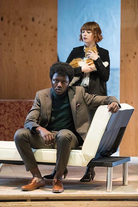 two actors on stage, one sitting on a couch and the other holding a cat