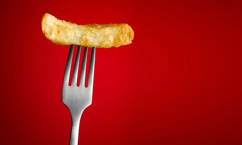too illustrate teen eating disorders, a photo of a fork against a bright red background, holding a single french fry