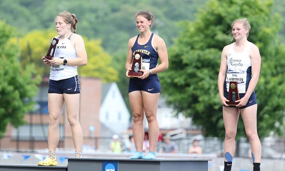 three student athletes standing on a podium with Rochester's Kylee Bartlett in the center spot