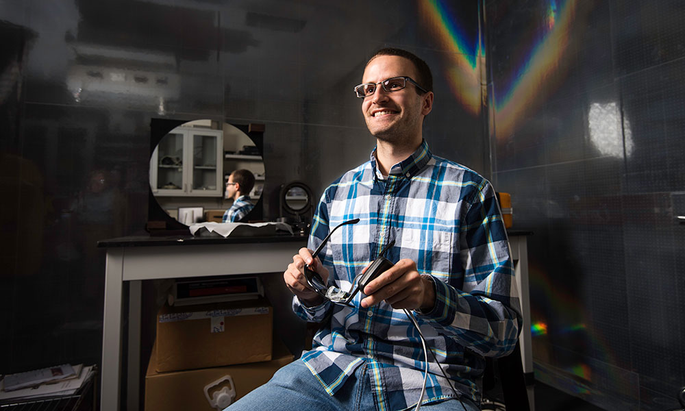 Aaron Bauer in his lab holding glasses and surrounded by lenses