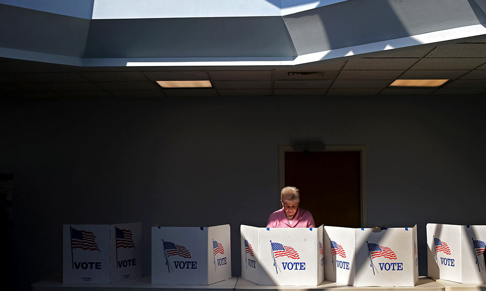 women stanbds behind a row of voting booths