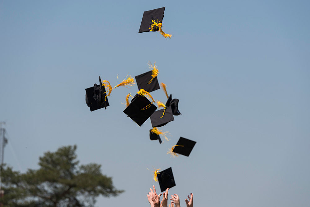 graduation caps being thrown into the air