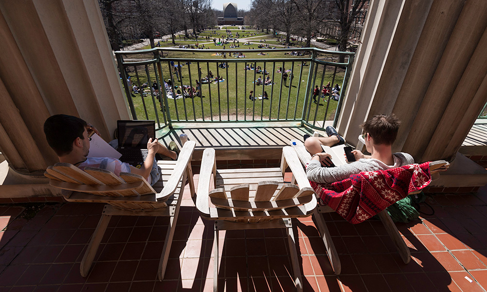 students sitting on Adirondack chairs on the library balcony on a sunny day
