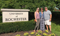 a family next to a University of Rochester sign