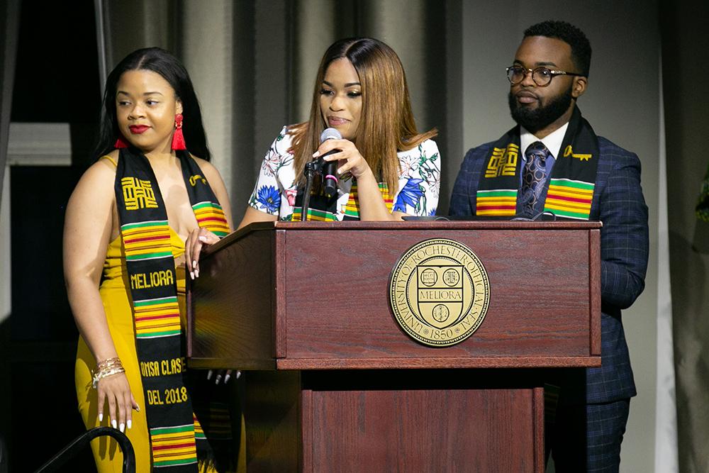 three students behind the podium