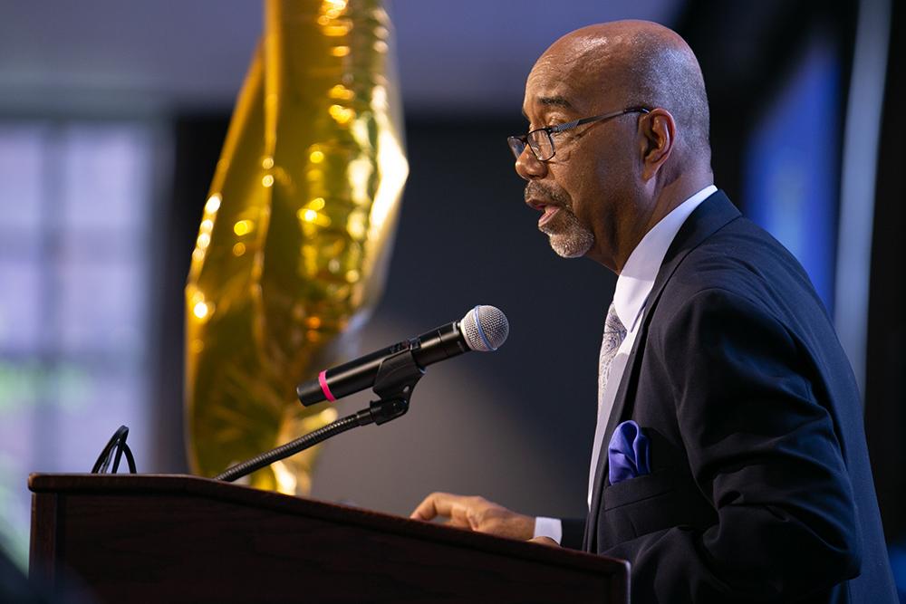 Norman Burnett speaking at a podium