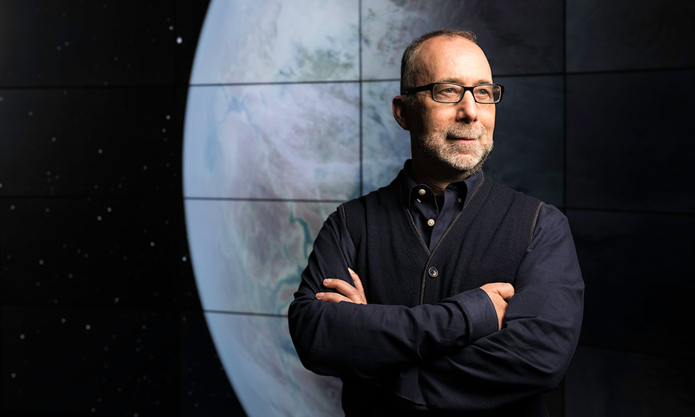 Adam Frank standing in front of a screen with a large photo of the Earth