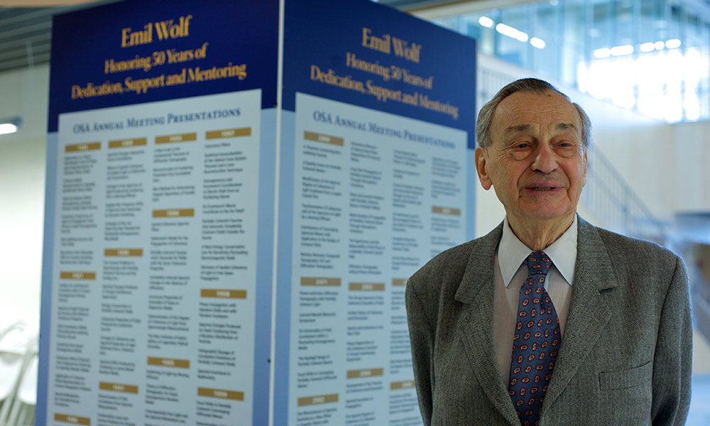 Emil Wolf standing in front of a sign marking hig 50th anniversary as a Rochester faculty member