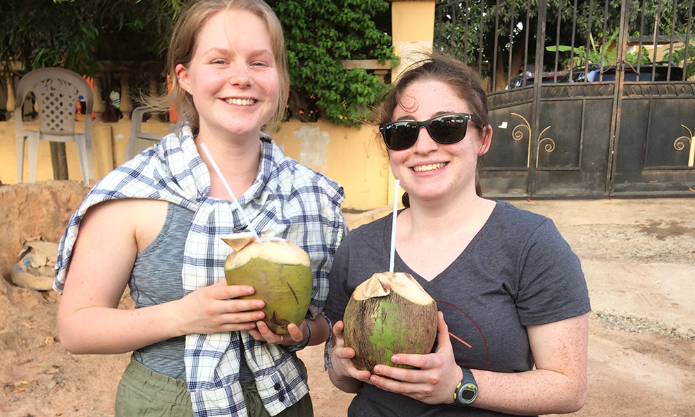 two students smiling and drinking out of coconuts with a straw