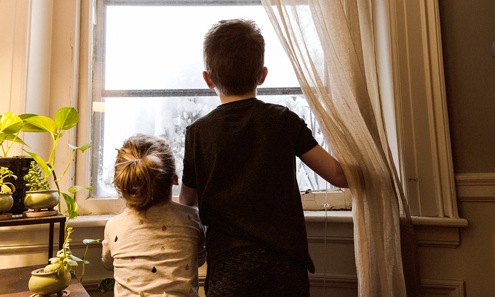 older brother and younger sister looking out a window